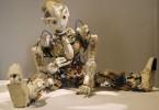 Człekokształtny robot, siedzący w rozkroku i patrzący na coś z zainteresowaniem