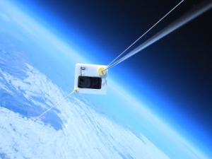 Telefon podwieszony pod balonem. Pod nim widziana z dużej wysokości powierzchnia Ziemii.